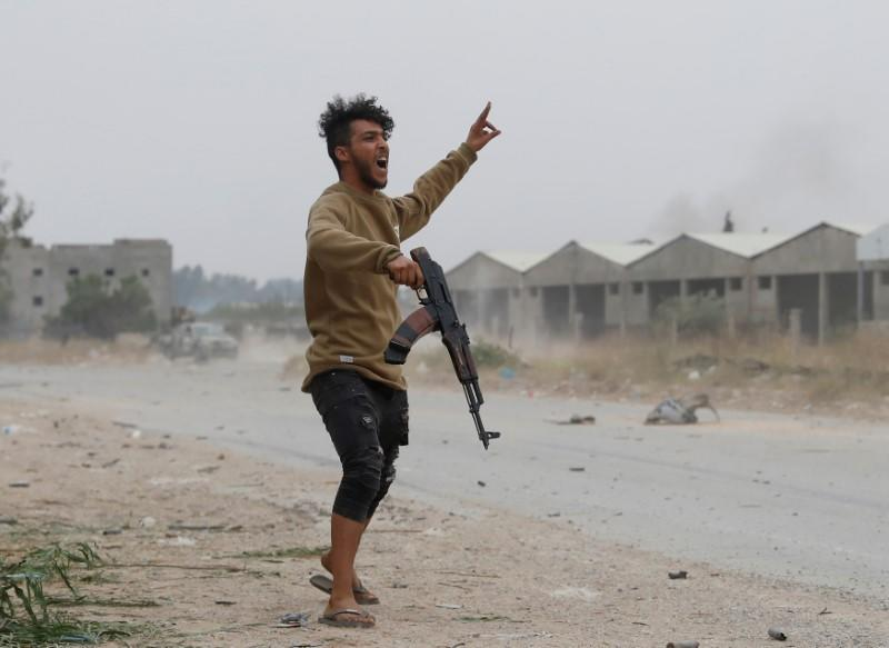 FILE PHOTO: A fighter loyal to Libya's U.N.-backed government (GNA) gestures during a clash with forces loyal to Khalifa Haftar at the outskirts of Tripoli