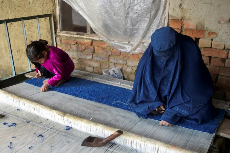An Afghan refugee woman and her daughter make carpet at her home in a refugee camp in Peshawar
