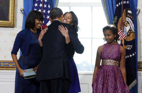 President Barack Obama hugs daughter Malia as first lady Michelle Obama and daughter Malia watch after Obama was officially sworn-in by Chief Justice John Roberts, not pictured, in the Blue Room of the White House during the 57th Presidential Inauguration in Washington, Sunday, Jan. 20, 2013. (AP Photo/Larry Downing, Pool)