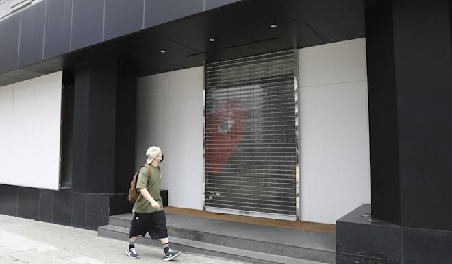 A man passes by a closed outlet of fashion retailer I.T in Causeway Bay on Monday. Photo: Nora Tam