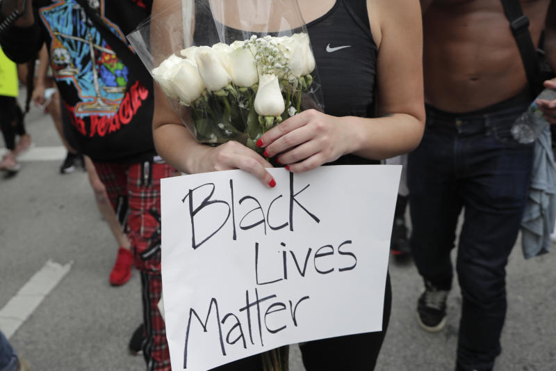A woman carries a bouquet of flowers as she marches during a protest over the death of George Floyd, Saturday, June 6, 2020, in Miami. Protests continue throughout the country over the death of Floyd, a black man who died after being restrained by Minneapolis police officers on May 25. (AP Photo/Lynne Sladky)
