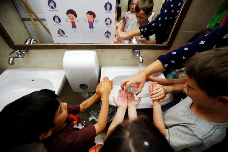 Teacher shows children how to wash their hands at her kindergarten in Jerusalem