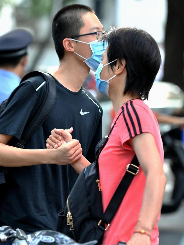 Seorang ibu menyemangati anaknya di luar lokasi ujian masuk perguruan tinggi di Sekolah Menengah Atas No. 2 Fuzhou di Fuzhou, ibu kota Provinsi Fujian, China tenggara (7/7/2020). Ujian masuk perguruan tinggi nasional China tahun ini telah dimulai pada Selasa (7/7). (Xinhua/Wei Peiquan)