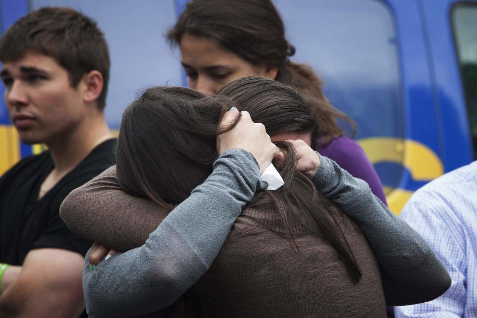 Sisters of Victoria Soto, who was killed in the Sandy Hook Elementary School shooting, embrace during the six-month anniversary of the massacre in Newtown
