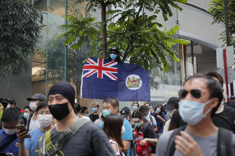 A man displays the Hong Kong colonial flag on the anniversary of Hong Kong's handover to China from Britain in Hong Kong, Wednesday, July. 1, 2020. Hong Kong marked the 23rd anniversary of its handover to China in 1997, and just one day after China enacted a national security law that cracks down on protests in the territory. (AP Photo/Kin Cheung)