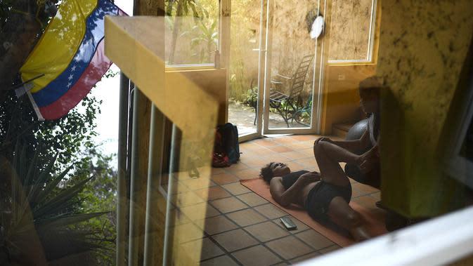 Peraih medali Olimpiade 2016 yang juga atlet BMX asal Venezuela, Stefany Hernandez menjalani terapi relaksasi otot dari seorang fisioterapis di rumahnya di Caracas pada 25 April 2020. Selain pernah meraih perunggu Olimpiade, Hernandez merupakan juara dunia BMX 2015. (AP/Matias Delacroix)