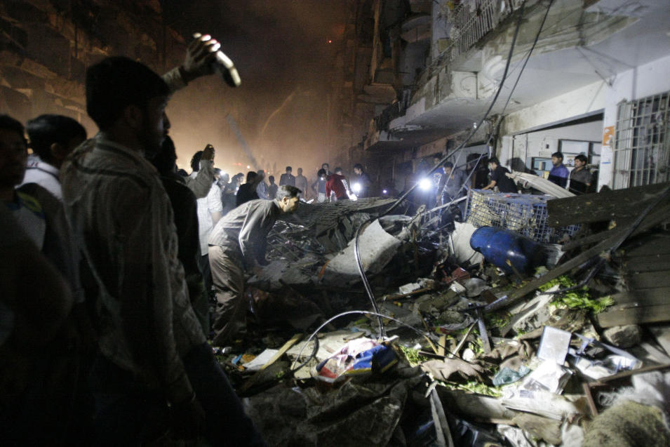Pakistani check the site of a bomb blast in Karachi, Pakistan, Sunday, March 3, 2013. Pakistani officials say a bomb blast has killed dozens of people in a neighborhood dominated by Shiite Muslims in the southern city of Karachi. (AP Photo/Fareed Khan)