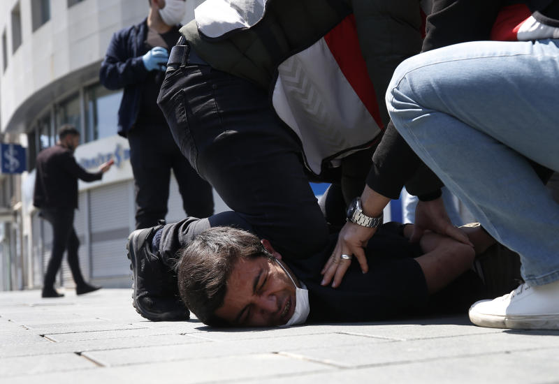 FILE - In this May 1, 2020, file photo, Turkish police officers arrest a demonstrator wearing a face mask for protection against the coronavirus, during May Day protests near Taksim Square, in Istanbul. The death of George Floyd has renewed scrutiny of immobilization techniques long used in policing around the world. (AP Photo/Emrah Gurel, File)