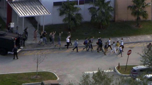 PHOTO: People emerge from a building with their hands raised after reports of a shooting at Stoneman Douglas High School in Parkland, Fla., Feb. 14, 2018. (WPLG)