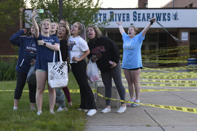 South River High School Class of 2020 seniors take a group photo after decorating their school during a senior prank at South River High School in Edgewater, Md., Wednesday, May 13, 2020. Despite the closure of the school because of the coronavirus pandemic, the students are finding way to keep traditions alive while their family and friends are finding new ways to celebrate and recognize their seniors. (AP Photo/Susan Walsh)