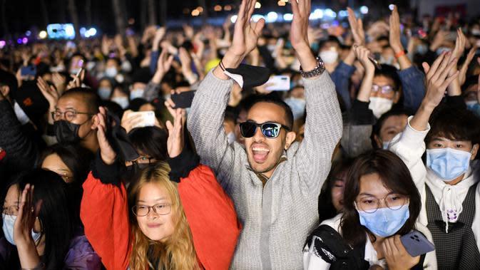 Orang-orang bereaksi saat sebuah band tampil pada Festival Musik Rye yang digelar selama dua hari di Beijing pada 18 Oktober 2020. (Photo by Noel Celis / AFP)