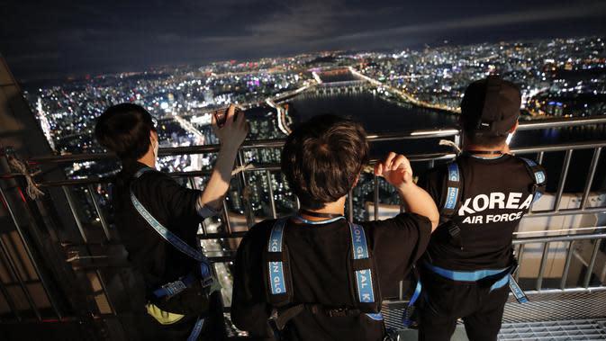 Orang-orang melihat pemandangan malam Seoul saat mereka menginap di tempat berkemah semalam di atap gedung pencakar langit di Seoul, Korea Selatan (7/8/2020). (AP Photo/Lee Jin-man)