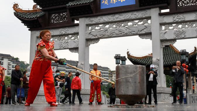 Seorang anggota Klub Gasing Kylin Guiyang memainkan sebuah gasing raksasa di Lapangan Jiaxiulou di Guiyang, Provinsi Guizhou, China barat daya, (15/5/2020). Agar gasing raksasa itu dapat berputar tanpa henti, sedikitnya 20 orang harus memutarnya secara bergantian. (Xinhua/Ou Dongqu)