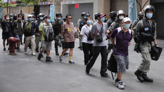 Polisi menahan pengunjuk rasa yang menentang Undang-Undang Keamanan Nasional pada hari peringatan penyerahan Hong Kong ke China dari Inggris di Hong Kong, Rabu (1/7/2020). (AP Photo/Kin Cheung)