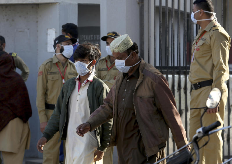 People and private guards wear masks while gather outside a hospital, where victims of toxic gas leak, are treated in Kamari neighborhood of Karachi, Pakistan, Monday, Feb. 17, 2020. A toxic gas leak killed five people and sickened dozens of others in a coastal residential area in Pakistan's port city of Karachi, police said Monday. The source of the leak, which occurred on Sunday night, and the type of gas that had leaked were not immediately known. There was no suspicion of sabotage. (AP Photo/Fareed Khan)