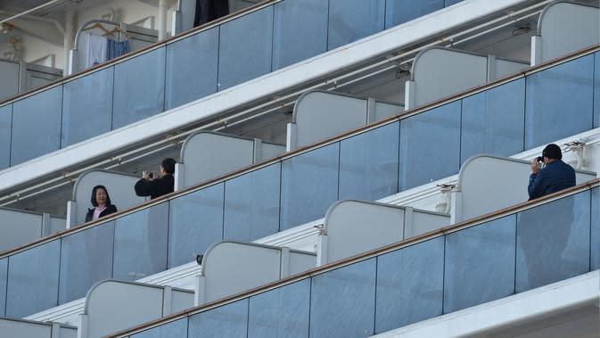 Penumpang foto di balkon kapal pesiar Diamond Princess saat dikarantina Daikoku Pier Cruise Terminal di Yokohama (7/2/2020). Ribuan penumpang terpaksa harus dikarantina setelah seorang penumpang yang turun di Hong Kong pada Januari lalu dinyatakan positif terinfeksi Corona. (AFP/Jiji Press)