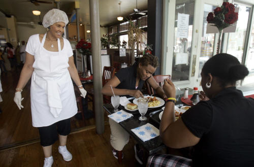 In this Saturday, July 28, 2007, file photo, Robbie Montgomery, left, talks to diners Tasha Davis, center, and Sylvona Harvey, right, in Sweetie Pie's, Montgomery's soul food restaurant. Turning small business owners into stars has become a winning formula for television producers, but some businesses featured in them are cashing in, too. Sales explode after just a few episodes air, transforming these nearly unknown small businesses into household names. (AP Photo/Jeff Roberson)