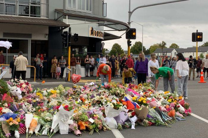 People place flowers at a growing makeshift memorial at a police roadblock.