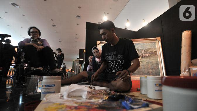 Seniman menyelesaikan karya lukis saat mengikuti Indonesian Art Festival