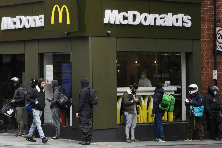 Delivery riders queue  outside a McDonald's in London; the company is facing a sexual harassment complaint filed at the OECD by an international coalition of labor unions