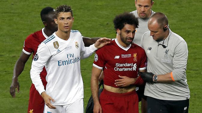 Striker Real Madrid, Cristiano Ronaldo, mendampingi Mohamed Salah saat ditarik keluar lapangan pada laga final Liga Champions di Stadion NSC Olimpiyskiy, Kiev, Minggu (27/5/2018). Salah mengalami cedera bahu usai dilanggar Ramos. (AP/Darko Vojinovic)