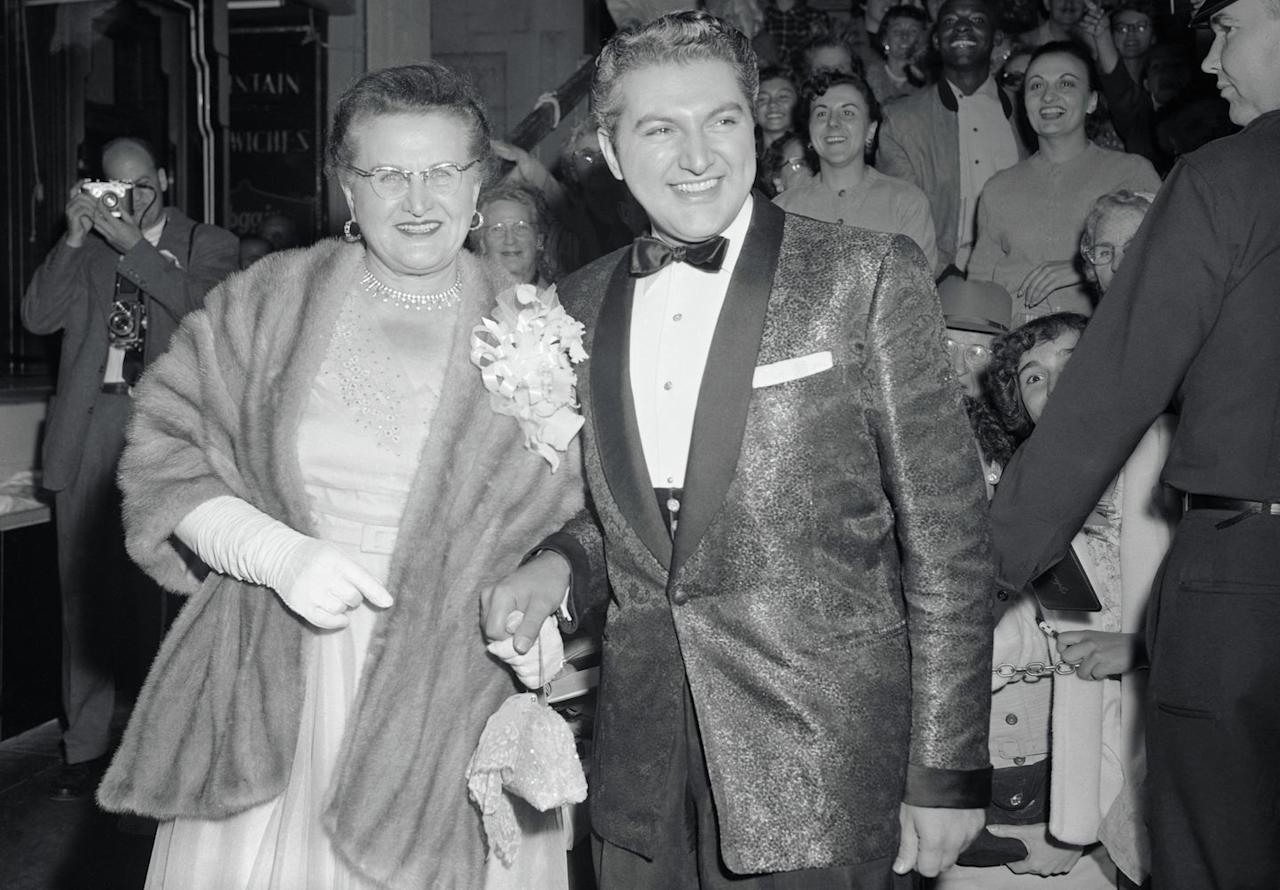 <p>Liberace walks down the red carpet at a film premiere alongside his mother, circa 1953.</p>