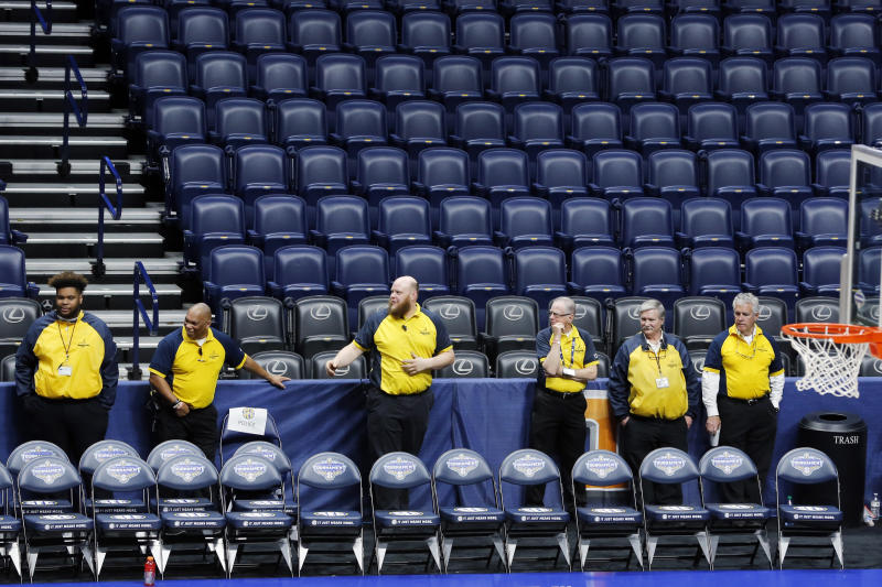 Security guards stand behind a team bench area at Bridgestone Arena after the NCAA college basketball games at the Southeastern Conference men's tournament were cancelled, Thursday, March 12, 2020, in Nashville, Tenn. The tournament was cancelled due to coronavirus concerns.  (AP Photo/Mark Humphrey)