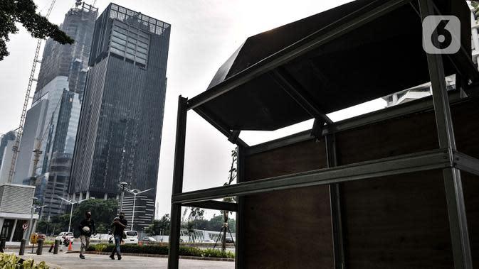Warga berjalan dekat Tugu Peti Mati Covid-19 di kawasan Sudirman, Jakarta, Minggu (6/9/2020). Dinas Kesehatan DKI Jakarta menyatakan positivity rate Covid-19 pada sepekan terakhir naik 13,1 persen atau melebihi standar yang ditetapkan WHO yakni lima persen. (merdeka.com/Iqbal S. Nugroho)