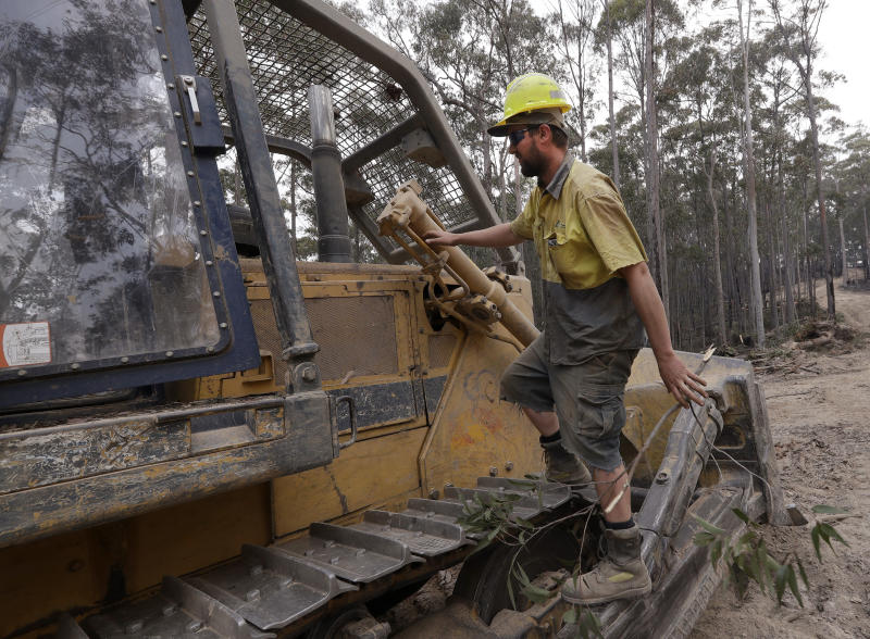 "A bulldozer operator that goes by the name ""Emu"" climbs on his dozer as he works at building a containment line at a fire near Bodalla, Australia, Sunday, Jan. 12, 2020. Authorities are using relatively benign conditions forecast in southeast Australia for a week or more to consolidate containment lines around scores of fires that are likely to burn for weeks without heavy rainfall. (AP Photo/Rick Rycroft)"