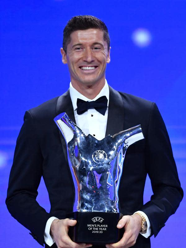 Penyerang Bayern Munchen Robert Lewandowski tersenyum saat menerima penghargaan Pemain Terbaik UEFA dalam acara UEFA Awards di Genewa, Swiss (1/10/2020). (Harold Cunningham / AFP / UEFA)