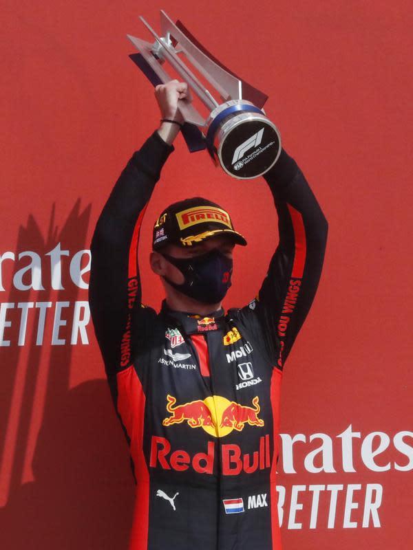Pembalap Red Bull Max Verstappen mengangkat trofi usai memenangkan 70th Anniversary Formula 1 Grand Prix di Sirkuit Silverstone, Silverstone, Inggris, Minggu (9/8/2020). Max Verstappen sukses menjadi yang tercepat dalam F1 GP Silverstone 2020. (AP Photo/Frank Augstein, Pool)