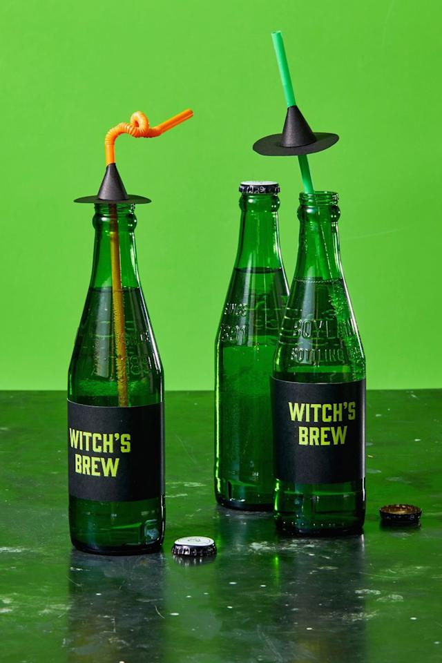 """<p>Make your soda or beer bottles fit for the party by taping our <strong><a href=""""https://hmg-prod.s3.amazonaws.com/files/ghkhalloween-witchesbrewwrappers-1564587124.pdf"""" target=""""_blank"""">Witch's Brew bottle wrap template</a> </strong>around the center of the bottle. If you want to go the extra mile, DIY witch hat straws: To make, cut two 3"""" circles out of black paper and punch a hole in the center of one. Slide a straw through the hole. Cut the other circle in half and roll to create a cone around the straw, glueing or taping in place. Glue or tape the cone to the paper circle to make it look like a witch hat.</p><p><strong>RELATED: </strong><a href=""""https://www.goodhousekeeping.com/holidays/halloween-ideas/g565/halloween-party-ideas/?"""" target=""""_blank"""">Ideas for the Best Halloween Party Ever </a></p>"""
