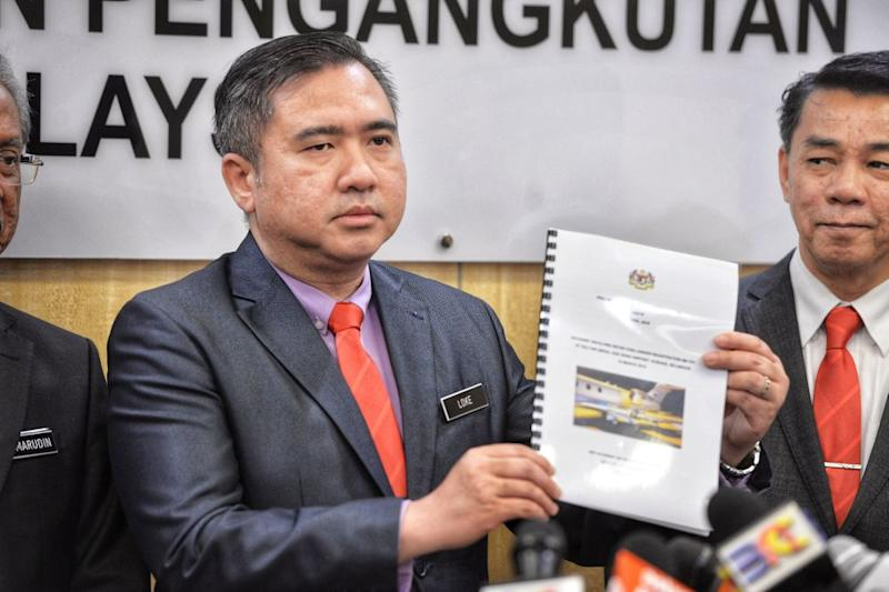 Transport Minister Anthony Loke holds up a copy of the report on the Subang Airport runway accident during a press conference in Putrajaya April 19, 2019. — Picture by Shafwan Zaidon