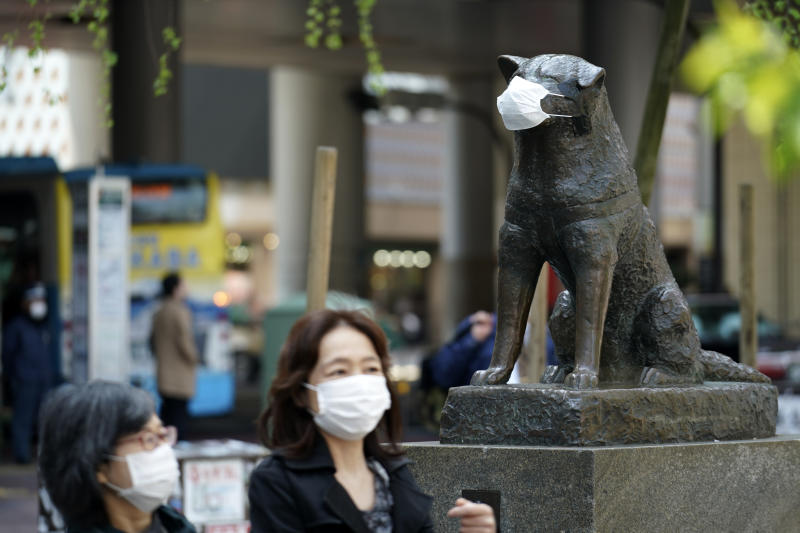 "A statue of a Japanese Akita dog named ""Hachiko"" wearing a face mask is seen near Shibuya Station Wednesday, April 8, 2020, in Tokyo. Japanese Prime Minister Shinzo Abe declared a state of emergency on Tuesday for Tokyo and six other prefectures to ramp up defenses against the spread of the new coronavirus. Hachiko has waited for his owner University of Tokyo Prof. Eizaburo Ueno at the same place by the station every afternoon, expecting him to return home for nearly 11 years even after Ueno's death at work. (AP Photo/Eugene Hoshiko)"