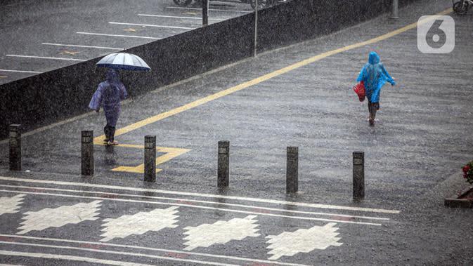 Warga berjalan saat turun hujan di Jalan Jenderal Sudirman, Jakarta, Minggu (18/10/2020). Badan Meteorologi, Klimatologi, dan Geofisika (BMKG) menyatakan musim hujan berlangsung mulai Oktober dan diprediksi mencapai puncaknya pada Januari hingga Februari 2021. (Liputan6.com/Faizal Fanani)