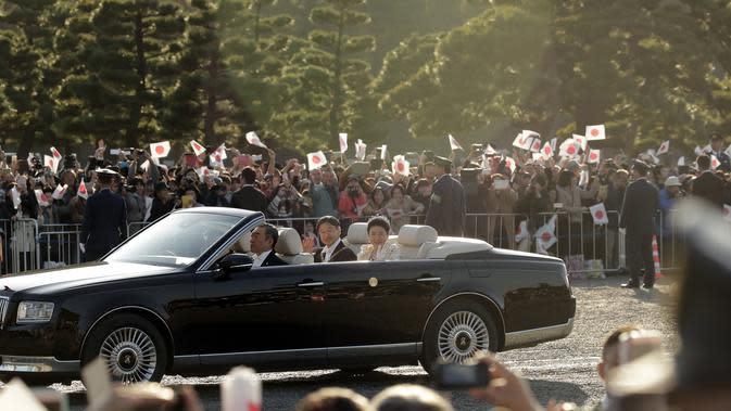 Kaisar Jepang, Naruhito dan Permaisuri Masako menyapa warganya selama parade di Tokyo, Jepang, Minggu (10/11/2019). Parade digelar dalam rangka mengakhiri serangkaian acara penobatan Kaisar Naruhito sejak 1 Mei 2019, atau sehari setelah Akihito turun takhta. (AP Photo/Jae C. Hong)