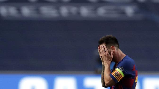 Striker Barcelona, Lionel Messi, menutup wajahnya usai ditaklukkan Bayern Munchen pada laga perempat final Liga Champions di Estadio da Luz, Sabtu (15/8/2020). Barcelona takluk 2-8 dari Bayern Munchen. (Manu Fernandez/POOL/AFP)