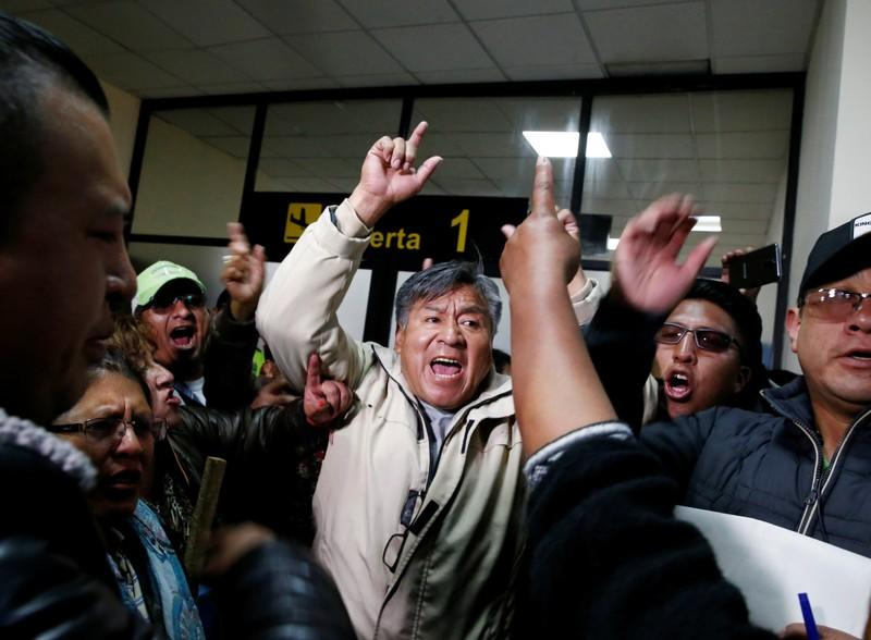 Supporters of Bolivia's President Evo Morales protest against Luis Fernando Camacho, President of Civic Committee of Santa Cruz, at the El Alto airport, on the outskirts of La Paz