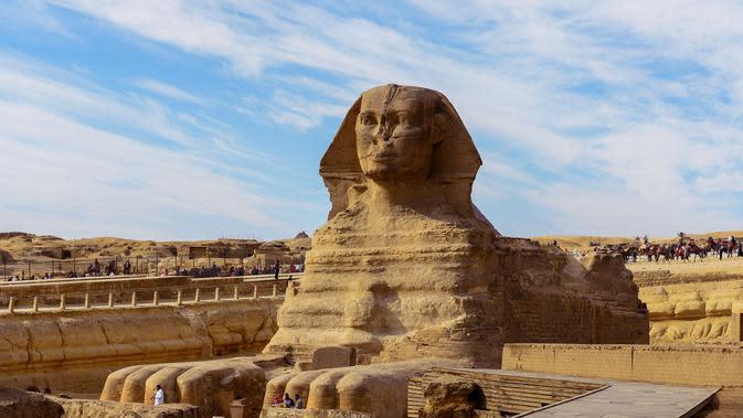 Sejumlah wisatawan melihat bangunan Sphinx di kompleks Piramida Giza di pinggiran Ibukota Kairo, Mesir (6/12). Di kompleks ini berdiri tiga Piramid besar ditambah satu buah Sphinx. (AFP Photo/Mohamed El-Shahed)