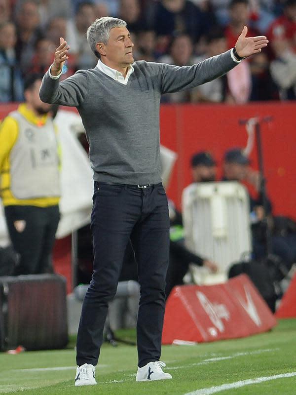Pelatih Real Betis Quique Setien bereaksi saat anak asuhnya menghadapi Sevilla FC pada pertandingan Liga Spanyol di Stadion Ramon Sanchez Pizjuan, Sevilla, Spanyol, 13 April 2019. Setien akan turun menangani Barcelona melawan Napoli pada babak 16 Besar Liga Champions. (CRISTINA QUICLER/AFP)