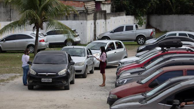 Antrean mobil berisi pasangan yang akan menjalani pernikahan drive-thru di kantor pencatatan sipil di Santa Cruz, Rio de Janeiro, Brasil, 28 Mei 2020. Fasilitas ini untuk memudahkan dan membantu pasangan yang ingin mengesahkan hubungan saat pandemi covid-19. (AP/Silvia Izquierdo)