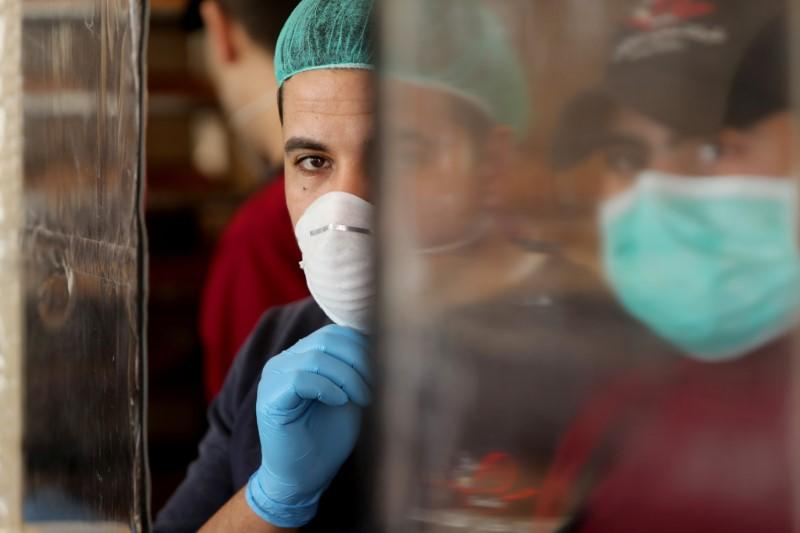 Palestinians, wearing masks as a preventive measure against the coronavirus disease, work in a bakery in Gaza City