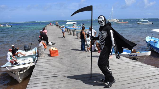 Seorang pria muda yang menyamar sebagai malaikat maut berkeliling pantai Puerto Morelos di Puerto Morelos, Quintana Roo, Meksiko, Sabtu (1/8/2020). Pria itu meminta wisatawan dan penduduk setempat kembali ke rumah karena pantai masih tertutup bagi pengunjung di tengah COVID -19. (ELIZABETH RUIZ/AFP)