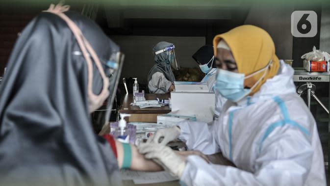 Petugas medis mengambil sampel darah saat rapid test Covid-19 di Stadion Patriot Candrabhaga, Bekasi, Rabu (23/9/2020). Rapid test yang digelar secara gratis oleh Pemkot Bekasi tersebut mampu memeriksa hingga 150 orang tiap harinya guna melacak kasus Covid-19 di Bekasi. (merdeka.com/Iqbal Nugroho)