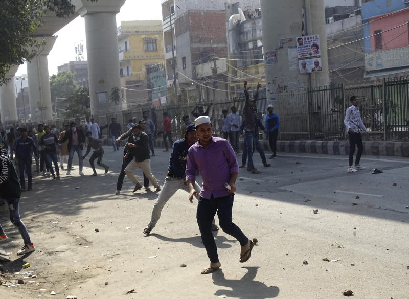 A group of protestors clash with another group in New Delhi, India, Monday, Feb. 24, 2020. Indian paramilitary troops used tear gas and smoke grenades to disperse a crowd of clashing protesters in New Delhi on Monday as violence broke out over a new citizenship law just ahead of U.S. President Donald Trump's visit to the city. (AP Photo/Dinesh Joshi)