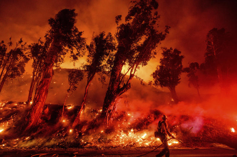 FILE - This Nov. 1, 2019, file photo shows flames from a backfire on a hillside as firefighters battle the Maria Fire in Santa Paula, Calif. California Gov. Gavin Newsom is urging a federal judge to reject Pacific Gas and Electric's blueprint for getting out of bankruptcy and renewing his threat to lead a bid to turn the beleaguered utility into a government-run operation. PG&E is trying to dig out of a financial hole created by more than $50 billion in claims stemming from a series of catastrophic wildfires that have been blamed on the San Francisco company. (AP Photo/Noah Berger, File)
