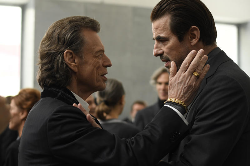 """This image released by Sony Pictures Classics shows Mick Jagger, left, and Claes Bang in a scene from the film, """"The Burnt Orange Heresy."""" Jagger plays a devilish art collector who cunningly convinces an art journalist, portrayed by Bang, to use a rare interview with a reclusive artist as an opportunity to steal one of his paintings. It's Jagger's first film since 2001's """"The Man From Elysian Fields.""""  (Jose Haro/Sony Pictures Classics via AP)"""