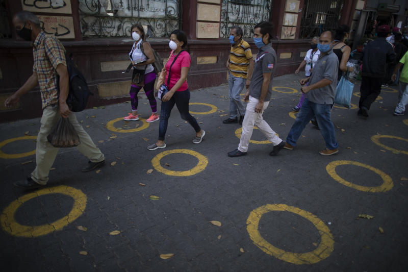 Yellow circles on a pavement serve as visual cues to help shoppers adhere to social distancing when lines form, to curb the spread of the new coronavirus, near a popular market in Caracas, Venezuela, Saturday, May 23, 2020. Evidence is mounting that these type of markets contributed to the spread of coronavirus in Latin America. (AP Photo/Ariana Cubillos)