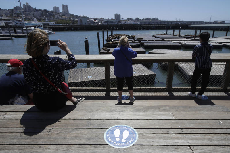 """FILE - In this June 18, 2020, file photo, a sign advising visitors to maintain social distance is shown as people watch the sea lions at Pier 39, where some stores, restaurants and attractions have reopened, during the coronavirus outbreak in San Francisco. Health officials in Santa Clara County, California, one of the most aggressive in the nation in shutting down because of the coronavirus are warning of """"worrisome"""" growing infections tied in the San Francisco Bay Area as California reports its highest one-day total infections amid a rise in hospitalizations from the virus. (AP Photo/Jeff Chiu, File)"""