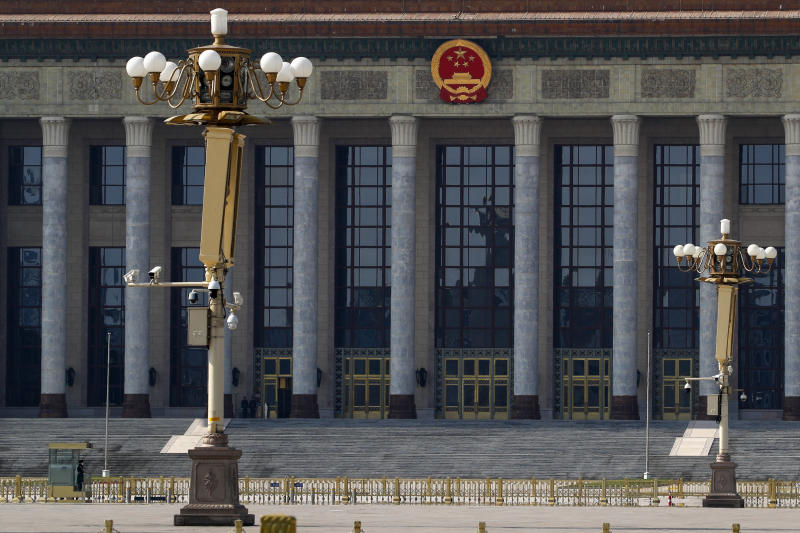 In this Sunday, Feb. 23, 2020, photo, a paramilitary policeman stands guard on a deserted Tiananmen Square against the Great Hall of the People in Beijing. China announced Monday it has postponed its most important political meeting of the year because of the outbreak of the new virus. (AP Photo/Andy Wong)